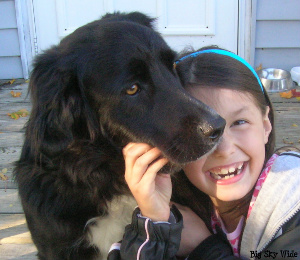 Black dog, smiling girl